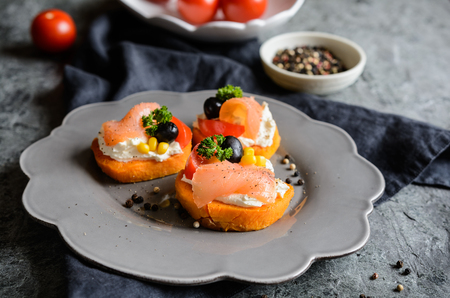 Baked Sweet potato slices topped with cream cheese, smoked salmon, olives and corn