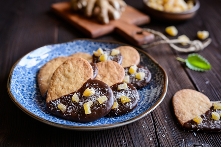 Heart shaped ginger biscuits decorated with chocolate and pieces of candied ginger