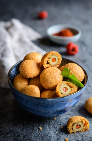 Baked green olives coated in cheese and paprika dough Stock Photo