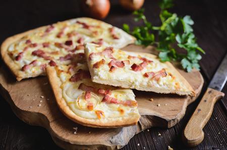 Tarta flambeada tradicional con crème fraiche, queso, cebolla y rodajas de tocino