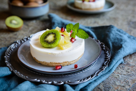 Delicious unbaked mini cheesecakes topped with pineapple, kiwi and pomegranate Stockfoto
