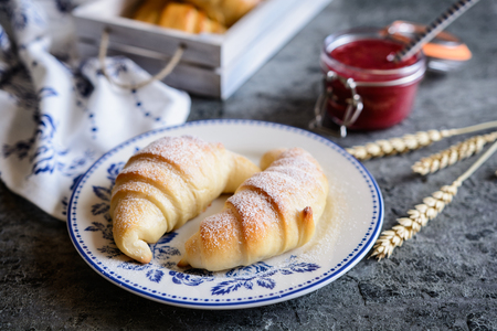 Traditional freshly baked croissants served with raspberry jam and butter Stock Photo