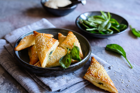 Freshly baked Spanakopita triangles stuffed with spinach and Feta cheese