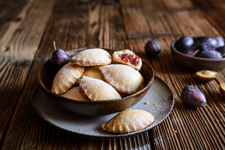 Delicious plum pocket pies studded with powdered sugar Stock Photo