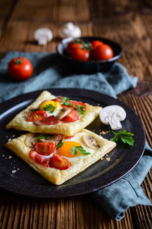 Savory puff pastry pies with egg, bacon, mushrooms and tomato