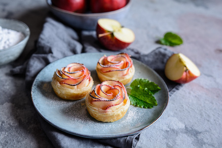 Delicious Rose shaped apple pies with powdered sugar dusting 写真素材