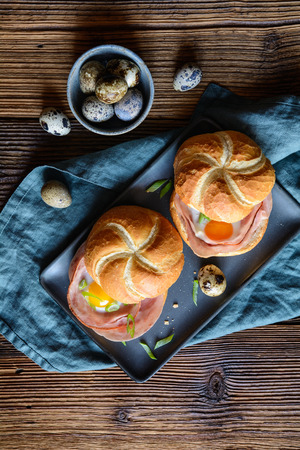Baked rolls stuffed with slices of ham, quail eggs and green onion