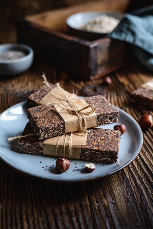Raw chocolate chia seeds bars with hazelnuts, rolled oats, dates, coconut and honey Stock Photo