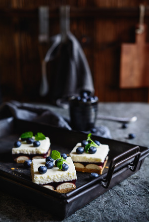 Delicious cake with layer of sponge biscuits, blueberry jelly, and whipped cream