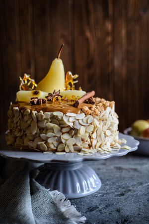 Delicious layered cake with caramel glaze, decorated with almond slices, pears, spun sugar decorations and cinnamon sticks Stock Photo