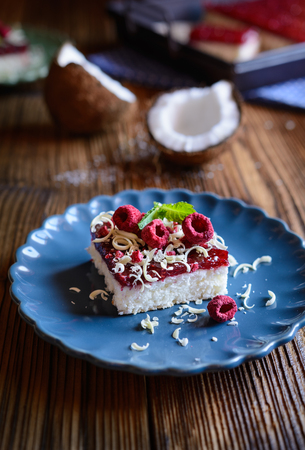 Delicious coconut cake with raspberry layer, topped with white chocolate shavings and freeze - dried raspberries