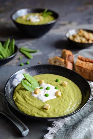 Delicious creamy green pea soup with sour cream