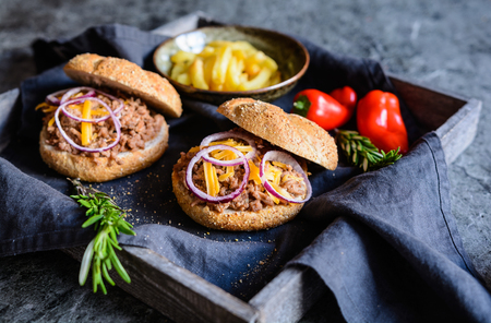 Homemade Sloppy Joe sandwich sprinkled with Cheddar cheese and onion, served with French fries