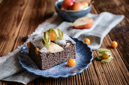 Poppy seed sponge cake with physalis and pear, sprinkled with powdered sugar Stock Photo