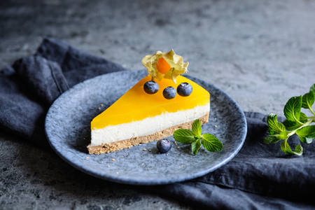 Homemade no bake mango cheesecake decorated with blueberries and physalis