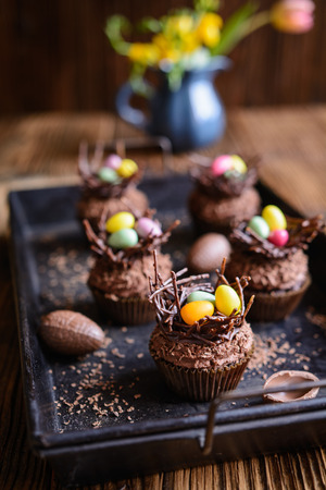 Easter nest cupcakes with chocolate whipped cream, decorated with colorful eggs Stock Photo - 119654989