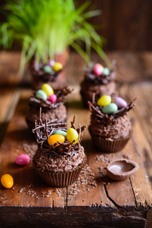 Easter nest cupcakes with chocolate whipped cream, decorated with colorful eggs Stock Photo - 119654991