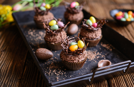 Easter nest cupcakes with chocolate whipped cream, decorated with colorful eggs