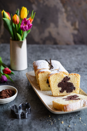 Sweet vanilla pound cake with Easter bunny inside, sprinkled with powdered sugar Stock Photo - 119969770