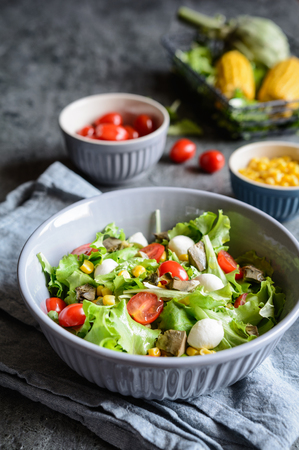Easy to make healthy salad with baked artichoke, Mozzarella, tomatoes and corn Stock Photo - 120554069