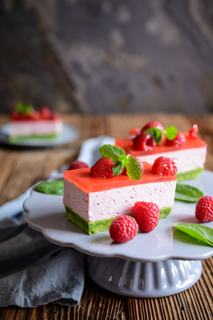 Sweet spinach cake with raspberry mousse and layer of jelly, decorated with fresh mint Stock Photo - 120554072