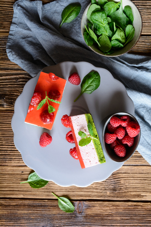 Sweet spinach cake with raspberry mousse and layer of jelly, decorated with fresh mint Stock Photo - 120554073
