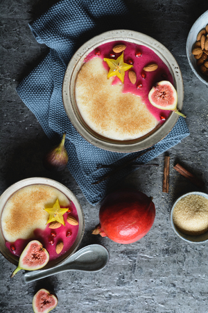 Semolina pudding with homemade pomegranate syrup, decorated with star fruit, figs and almonds Stock Photo - 120726412