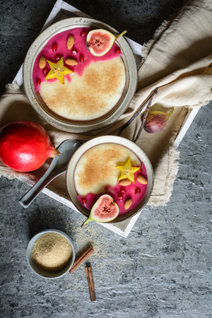 Semolina pudding with homemade pomegranate syrup, decorated with star fruit, figs and almonds Stock Photo - 120726413