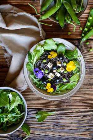 Vegetarian black bean pasta salad with leafy greens, olives, green peas, sheep cheese, decorated with edible flowers Stock Photo - 121313169