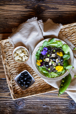 Vegetarian black bean pasta salad with leafy greens, olives, green peas, sheep cheese, decorated with edible flowers