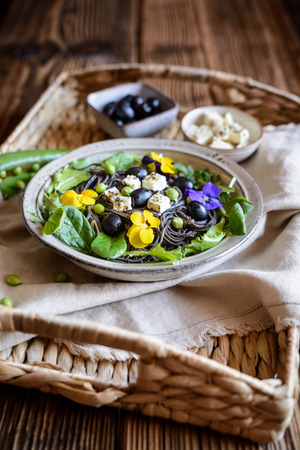 Vegetarian black bean pasta salad with leafy greens, olives, green peas, sheep cheese, decorated with edible flowers Stock Photo - 121313171