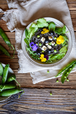 Vegetarian black bean pasta salad with leafy greens, olives, green peas, sheep cheese, decorated with edible flowers Stock Photo - 121313172