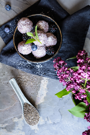 Sweet chia seed balls with blueberry and blackberry puree, coated with grated coconut