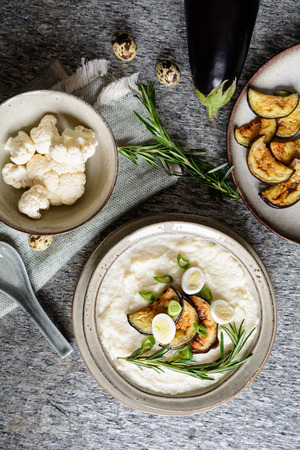 Delicious cauliflower puree with baked eggplant and quail eggs Stock Photo