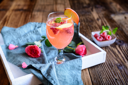 Refreshing raspberry peach mimosa drink on a wooden background