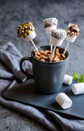 Homemade sweet marshmallow pops dipped in chocolate, sprinkled with pistachios, almonds and grated coconut