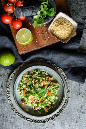 Refreshing vegetarian Tabbouleh salad with bulgur, parsley, mint, tomatoes and seasoning