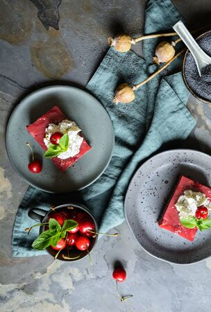 Delicious poppy seed cake with cherry custard on a rustic background Stock Photo - 126048954