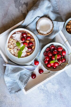 Healthy cherry coconut smoothie bowl with banana and almonds Stock Photo - 126799826