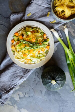 Vegetarian butter squash pasta salad with zucchini slices, scallion and topped with grated cheddar cheese Stock Photo
