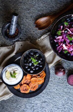 Fried sweet potato slices served with sour cream dip, black olives and salad made of red cabbage, red onion and beetroot