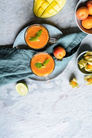 Refreshing cold drink, apricot smoothie with mango and physalis