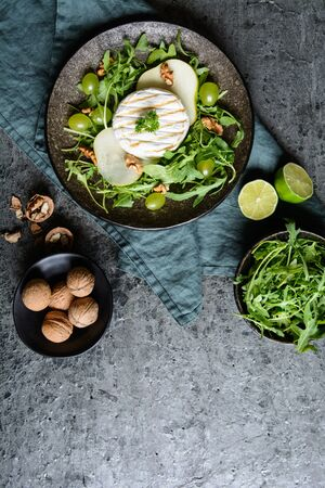 Grilled Camembert cheese, served with fresh arugula, green grapes, pears and walnut