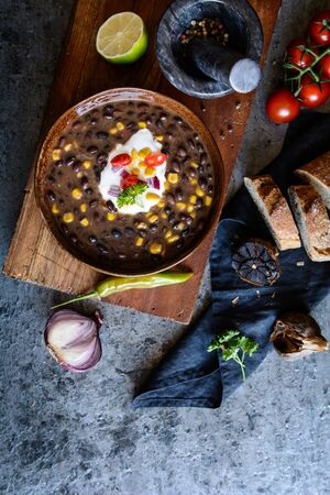 Vegetarian black bean soup with corn, tomatoes, sour cream, served with baguette Stock Photo