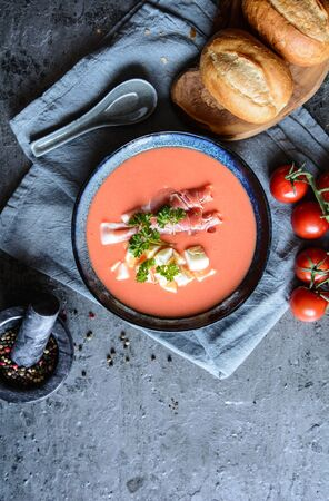 Salmorejo, cold tomato soup with Serrano ham and eggs in a ceramic bowl, served with pastry