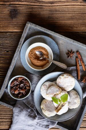Traditional Welsh cakes with raisins, sprinkled with powdered sugar on wooden background