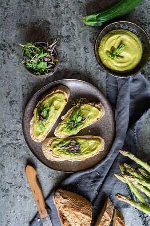 Slices of bread with vegetarian avocado, zucchini and asparagus spread, topped with pea and radish sprouts on a ceramic plate