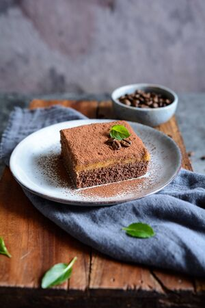 Dark chocolate dessert topped with coffee cream and sprinkled with cocoa powder on a ceramic plate