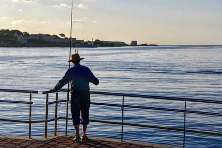 man fishing, view es castells, a town near Mahon, at sunrise