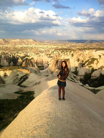 Woman with camera standing in Cappadocia landscape